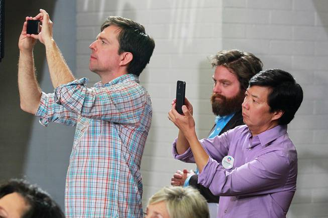 Actors Ed Helms, left, and Ken Jeong take cell phone photos while watching first lady Michelle Obama with fellow actor Zach Galifianakis at a campaign appearance for President Barack Obama, at Orr Middle School Friday, Oct. 26, 2012.