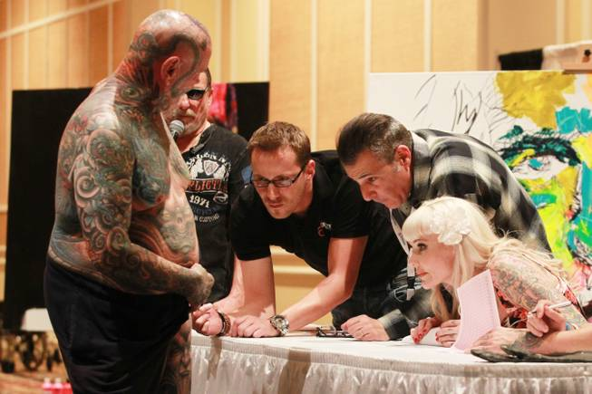 Milwaukee resident David Zielinski displays recent work for judges Mike Ehrmann, Paul Gambino and Sabina Kelley during a contest at Mario Barth's Biggest Tattoo Show on Earth at the Mirage on Saturday, Oct. 27, 2012.