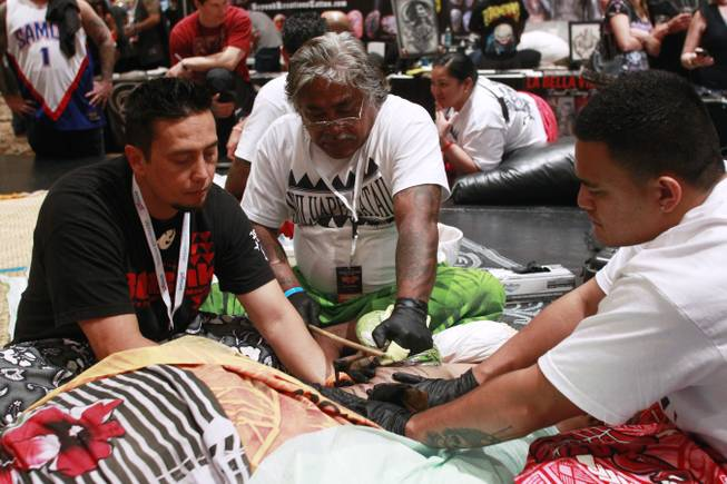 Master Tattooist Tufuga Su'a Alaiva'a Petelo Sulu'ape works on a woman's leg with traditional Samoan tattoo tools at while being assisted by Lane Wilcken, left, and Fesolai Imo Levi Mario Barth's Biggest Tattoo Show On Earth at the Mirage Saturday, Oct. 27, 2012.