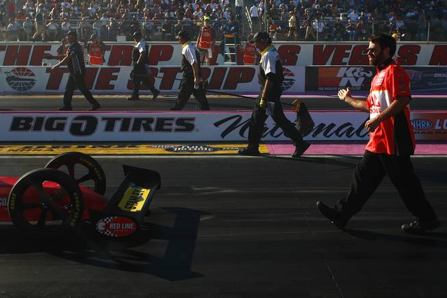 One of Doug Kalitta's crew members helps guide him back to the starting line during the 12th Annual Big O Tires Nationals NHRA drag race on The Strip at Las Vegas Motor SpeedwaySunday, Oct. 28, 2012.