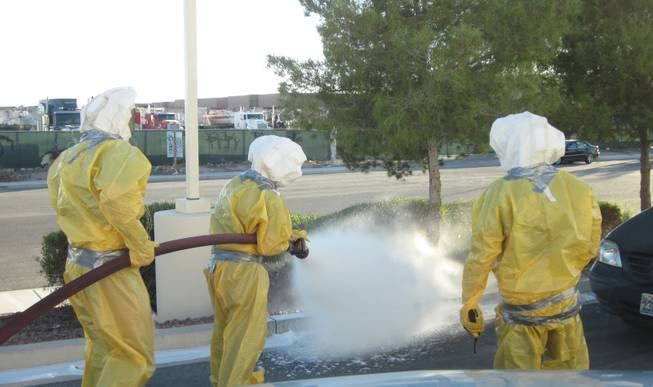 Clark County firefighters, outfitted in special clothing, douse a beehive with foam Sunday, Oct. 28, 2012, near Nellis Air Base. A group of children had disturbed the hive, housed in a sprinkler box, causing the bees to start attacking the children.