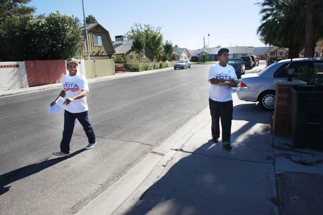 Mi Familia Vota canvassers Angel Escamilla, left, and Izack Tenorio look for voters Tuesday, Oct. 30, 2012.