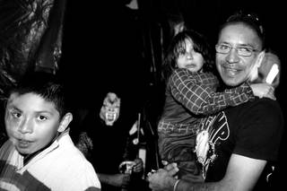 Arturo Martinez-Sanchez takes his sons Cristopher, left, 10, and Alejandro, 5, through a haunted house while trick-or-treating with friends from his old neighborhood in Las Vegas on  Oct. 31, 2012.