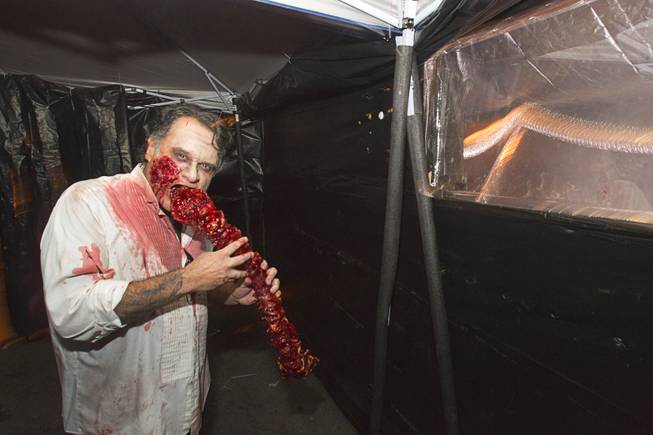 A zombie enjoys a snack in the Haunted Alley during Halloween in downtown Las Vegas Wednesday, October 31, 2012.