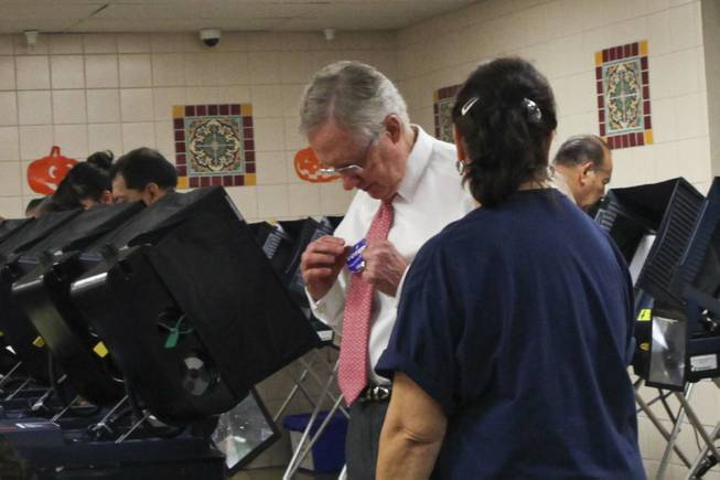 Sen. Harry Reid affixes an I voted sticker to his tie after casting an early vote at the Cardenas Market on East Bonanza polling station in Las Vegas on Wednesday, Oct. 31, 2012.