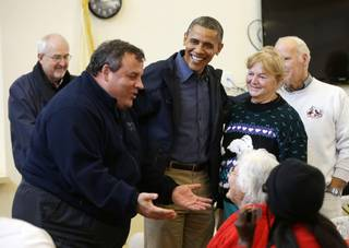 President Barack Obama, center, and the Federal Emergency Management Administration's Craig Fugate, left, watch as New Jersey Gov. Chris Christie, second from left, meets with residents at Brigantine Beach Community Center on Wednesday, Oct. 31, 2012, in Brigantine, N.J.