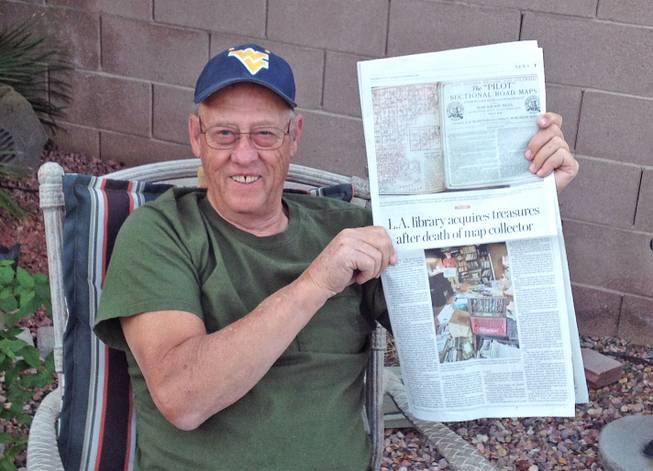 John Feathers holds a Los Angeles Times story printed in the Las Vegas Sun about his son, John E. Feathers, and his map collection.