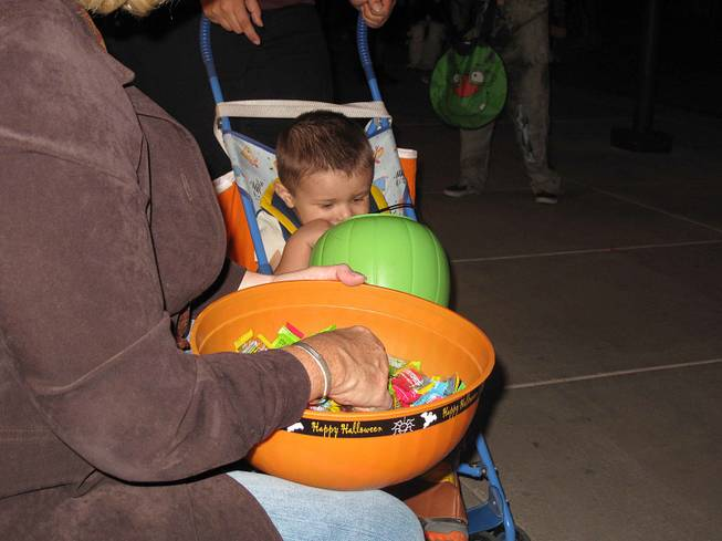 A young trick-or-treater checks out his Halloween loot at the District at Green Valley Ranch in Henderson, Wednesday, Oct. 31, 2012.