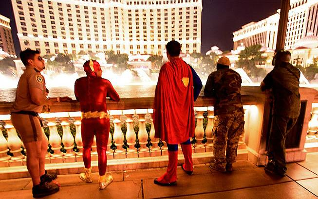 A costumed group out celebrating Halloween pauses to observe the Bellagio Fountains, Oct. 31, 2012.