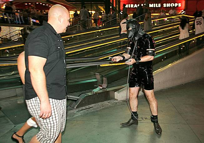 Adam Benson, of Leeds, England, wears a leather bondage suit and passes out handbiller cards on the Strip as part of a Halloween dare for his bachelor party, Oct. 31, 2012.