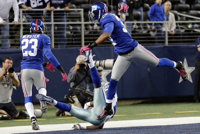 Dallas Cowboys wide receiver Dez Bryant (88) makes a last-minute reception between New York Giants cornerbacks Corey Webster (23) and Michael Coe (37) for a touchdown that was nullified after review during an NFL football game, Sunday, Oct. 28, 2012, in Arlington, Texas. Bryant's hand landed on the line. The Giants won 29-24.