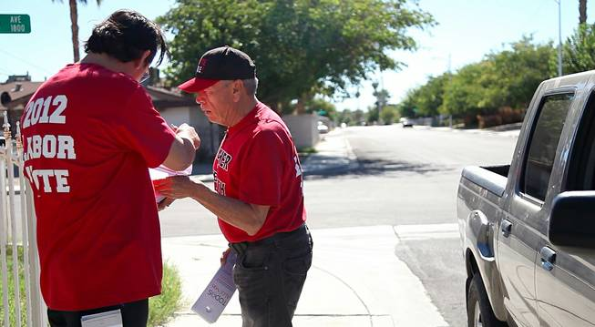 Culinary 226 members Moises Torres checks on his partner's list to make sure they haven't missed a house in the neighborhood they were stationed in on Nevada Day, knocking on doors of potential voters, Oct. 26, 2012.