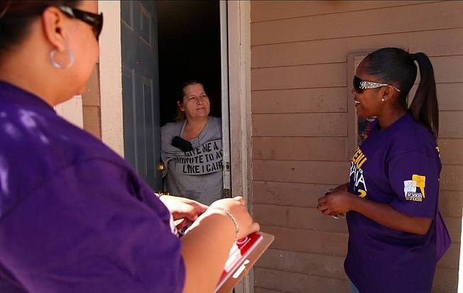 SEIU workers Rasheda Anthony, right, and Yolanda Florian, left, talk to a woman who has already decided to vote for President Barack Obama about the merits of early voting in North Las Vegas, Oct. 27, 2012.