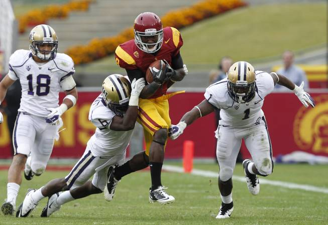 Southern California's Marquise Lee is tackled by Washington's Desmond Trufant after a 14-yard gain in the second half of an NCAA college football game, Saturday, Nov. 12, 2011, in Los Angeles. Southern California won 40-17.