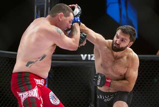 Heavyweight Devin Cole of Medford, Ore. takes a punch from Andrei Arlovski of Belarus during the World Series of Fighting debut at the PH Live theater at Planet Hollywood Saturday, Nov. 3, 2012. The event was broadcast live on the NBC Sports Network.