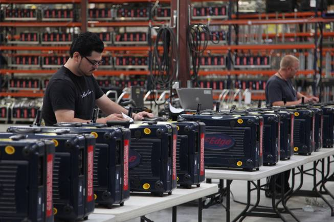 Maintenance workers on Saturday, Nov. 3, 2012, clean voting machines that have been brought back to the Clark County Elections Office after early voting ended. The machines will return to polling places for Election Day.