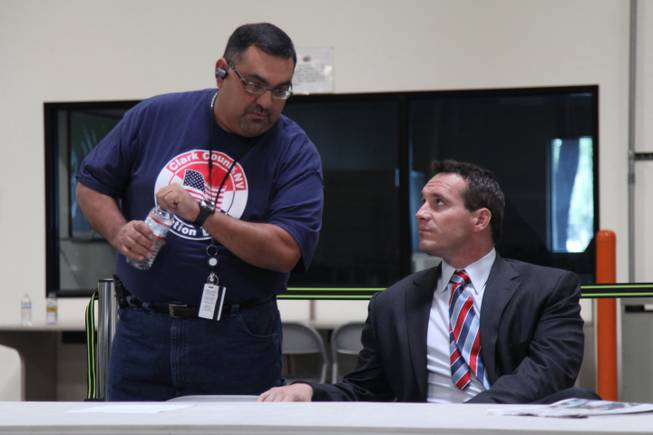Nevada Secretary of State Ross Miller, right, talks to Joe Gloria, who directs programming and maintenance for Clark County's elections division, before a news conference Saturday, Nov. 3, 2012.