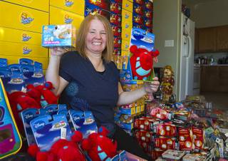Susan England poses with toys at her home Sunday, Nov. 4, 2012. England made a New Year's resolution to collect 100 toys for $100 to donate to the Toys For Tots charity. Then, after she reached the goal, she just kept on going she said.