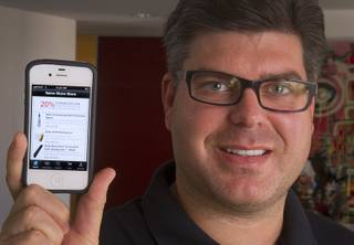 Tommy Bell, founder of SalonShare.com, holds a iPhone displaying his company's website at his office Monday, Nov. 5, 2012. Bell says says it can be quite hard for companies to get startup financing, largely because there is a small number of local tech investors.