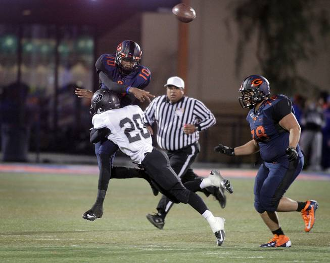 Randall Cunningham of Bishop Gorman makes a successful pass just before being tackled by Sean Dennis of Palo Verde during the Sunset Regional semifinals at Bishop Gorman High School in Las Vegas on Friday, November 9, 2012.
