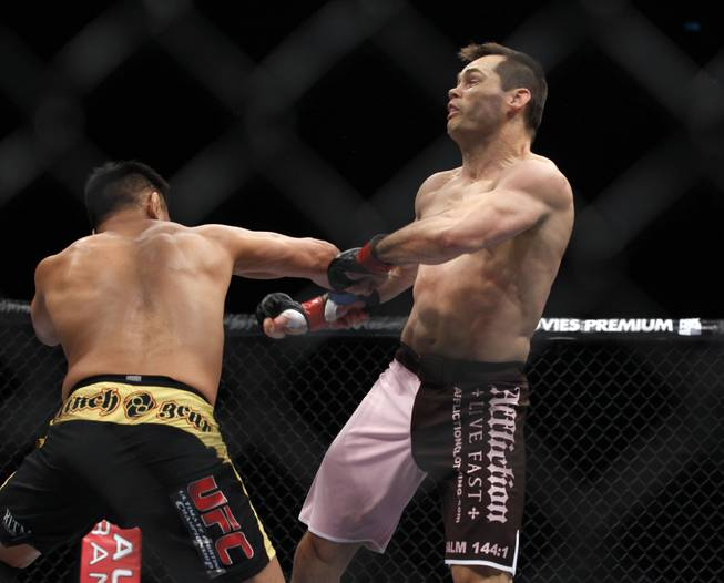 Cung Le, left, hits Rich Franklin during their middleweight Ultimate Fighting Championship match at the Venetian Macao in Macau on Saturday, Nov. 10, 2012. Le won by a knockout in the first round.