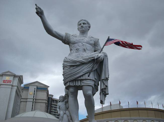 A statue of Caesar Augustus with the American flag welcomes guests at the main entrance of Caesars Palace on Friday, Nov. 9, 2012, in honor of Veterans Day.