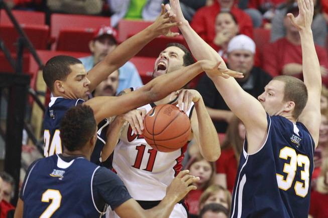 UNLV forward Carlos Lopez is trapped by Northern Arizona's, from left, Jordyn Martin, Michael Dunn and Max Jacobson during the Rebels season opener Monday, Nov. 12, 2012 at the Thomas & Mack. UNLV won 92-54.