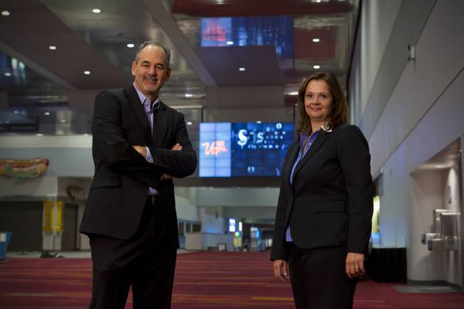 Mark Haley, President of Smart City Networks, and Jennifer Stefano, Manager of Digital Advertising, stand in front of the large digital wall in the Grand Concourse of the Las Vegas Convention Center, Tuesday Nov. 6, 2012.