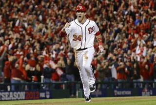 This Oct. 12, 2012 file photo shows Washington Nationals' Bryce Harper reacting as he heads home on a home run by Ryan Zimmerman during the first inning of Game 5 of the National League division baseball series against the St. Louis Cardinals in Washington.