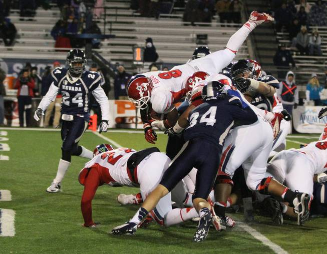 Fresno State's Robbie Rouse jumps over UNR's defensive line to score in the Bulldogs' 52-36 victory in Reno.