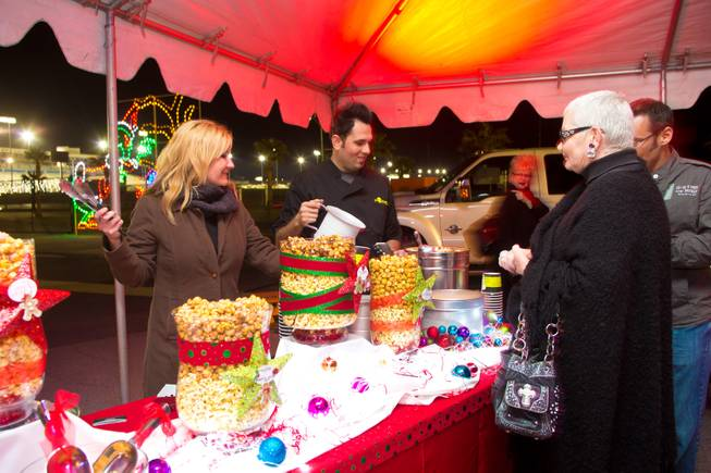 Zelma Watsubo and Oliver Morowati, of Popped, serve some of their gourmet popcorn during the ceremonial opening of the Glittering Lights show at Las Vegas Motor Speedway, Thursday, Nov. 15, 2012.