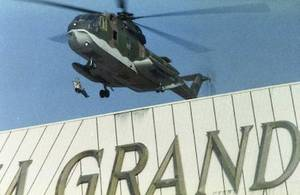 A person is seen hanging from a military helicopter as it flies over the MGM Grand sign during the Nov. 21, 1980, fire.