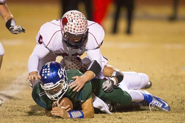 Green Valley quarterback Christian Lopez is sacked by Coronado defenders during the Sunrise regional semifinal at Green Valley High School in Henderson Friday, November 16 , 2012.