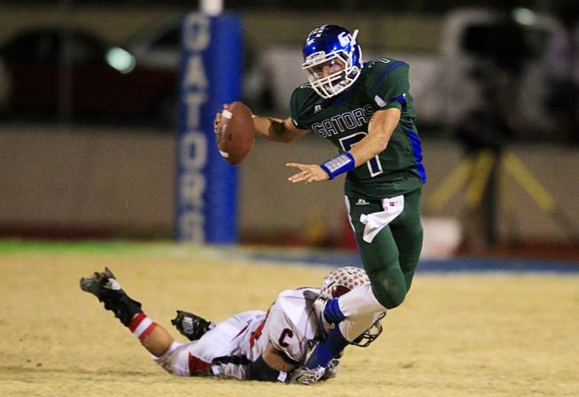 Coronado's Cosme Montenegro makes a diving tackle on Green Valley quarterback Christian Lopez during the Sunrise regional semifinal at Green Valley High School in Henderson Friday, November 16 , 2012.