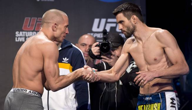 UFC welterweight champion George St-Pierre shakes hands with his opponent Carlos Condit during the weigh-in Friday, November 16, 2012 in Montreal. The two will fight in UFC 154 Saturday.