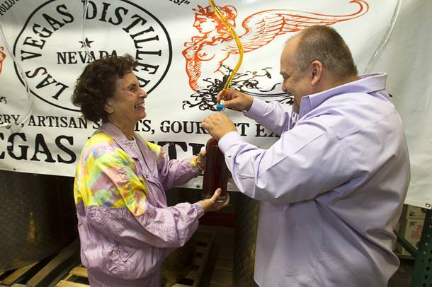 Beverly Brown gets help from Las Vegas Distillery founder George Racz as she fills the first bottle of Nevada whiskey during the Historic First Edition Day at the Las Vegas Distillery in Henderson Saturday, November 17, 2012. The event marks the first bottling of several new spirits and the grand opening of the Booze Brothers Beverage distribution company and the Half Full Artisan Shop at the Distillery, a retail store. The spirits include Nevada vodka, whiskey, gin, rum and moonshine.