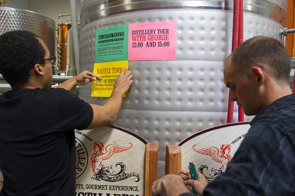 Workers posts signs as they get ready for the Historic First Edition Day at the Las Vegas Distillery in Henderson Saturday, November 17, 2012. The event marks the first bottling of several new spirits and the grand opening of the Booze Brothers Beverage distribution company and the Half Full Artisan Shop at the Distillery, a retail store. The spirits include Nevada vodka, whiskey, gin, rum and moonshine.