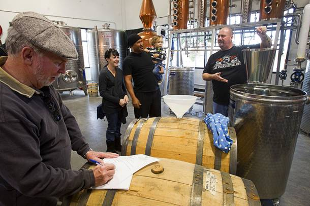 Bret Stanley, right, holds up a bucket of single malt whiskey as he invite guests to help fill a barrel during the Historic First Edition Day at the Las Vegas Distillery in Henderson Saturday, November 17, 2012. The whiskey will be aged for three years, he said.The event marks the first bottling of several new spirits and the grand opening of the Booze Brothers Beverage distribution company and the Half Full Artisan Shop at the Distillery, a retail store. The spirits include Nevada vodka, whiskey, gin, rum and moonshine.