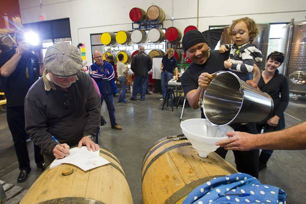 David Kekone, right, helps fill a barrel with single malt whiskey as his son Dante Xavier Kekone, 2, looks on during the Historic First Edition Day at the Las Vegas Distillery in Henderson Saturday, November 17, 2012. The event marks the first bottling of several new spirits and the grand opening of the Booze Brothers Beverage distribution company and the Half Full Artisan Shop at the Distillery, a retail store. The spirits include Nevada vodka, whiskey, gin, rum and moonshine.