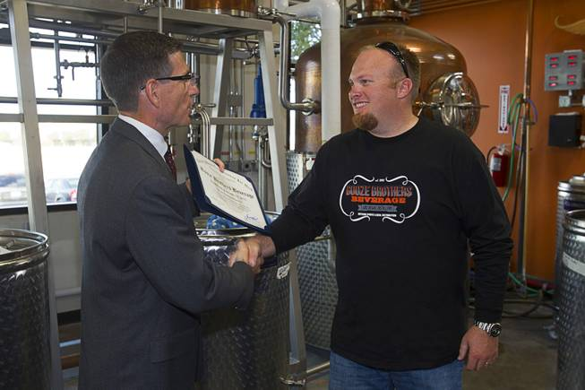 Congressman Joe Heck (R-NV), left, presents a certificate of recognition to Justin Wallin, owner of Booze Brothers Beverage, during the Historic First Edition Day at the Las Vegas Distillery in Henderson Saturday, November 17, 2012. The event marks the first bottling of several new spirits and the grand opening of the Booze Brothers  distribution company and the Half Full Artisan Shop at the Distillery, a retail store. The spirits include Nevada vodka, whiskey, gin, rum and moonshine.