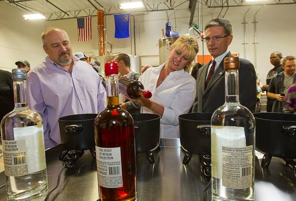 Las Vegas Distillery founder George Racz, left, looks on as Lisa Heck and her husband Congressman Joe Heck (R-NV) wax the top of a Nevada Whiskey bottle during the Historic First Edition Day at the Las Vegas Distillery in Henderson Saturday, November 17, 2012. The event marks the first bottling of several new spirits and the grand opening of the Booze Brothers Beverages distribution company and the Half Full Artisan Shop at the Distillery, a retail store. The spirits include Nevada vodka, whiskey, gin, rum and moonshine.
