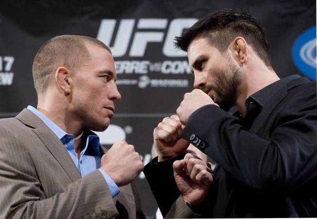 Georges St-Pierre, left, squares off with Carlos Condit following a press conference in Montreal, Wednesday, Nov. 14, 2012, ahead of their UFC 154 title fight in Montreal on Nov. 17.
