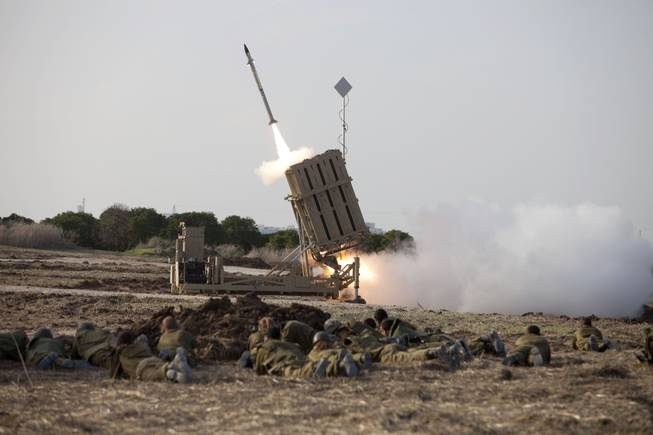 Israeli soldiers lie on the ground as an Iron Dome missile is launched near the city of Ashdod, Israel, Monday Nov 19, 2012.
