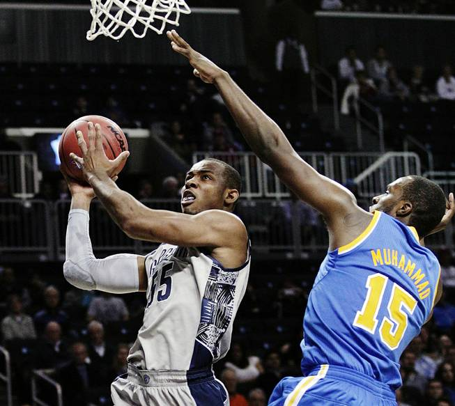 Georgetown's Jabril Trawick (55) drives past UCLA's Shabazz Muhammad (15) in the second half of their NCAA college basketball game in the Legends Classic, Monday, Nov. 19, 2012, in New York. Georgetown won 78-70.