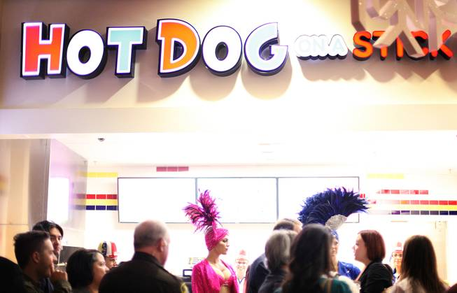 Former Mayor Oscar Goodman and his showgirls pose for photos in front of Hot Dog on a Stick during the grand opening of Castle Walk Food Court at the Excalibur in Las Vegas on Tuesday, November 20, 2012.