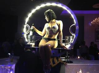 Champagne is served from a model who descends from the ceiling at the grand opening of Bagatelle nightclub and restaurant on Nov. 16, 2012, at the Tropicana.