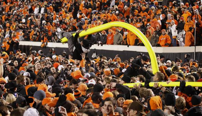 A fan hangs from a goal post after it was torn down in celebration of Oklahoma State's 44-10 win over Oklahoma in an NCAA college football game in Stillwater, Okla., Saturday, Dec. 3, 2011.