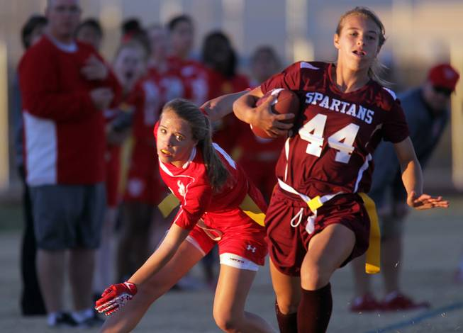 Francesca D'Arienzo, left, of Arbor View watches as Jaymee Luke of Cimarron-Memorial runs with the ball during their girls flag football game at Cimarron-Memorial High School on Monday, November 26, 2012.