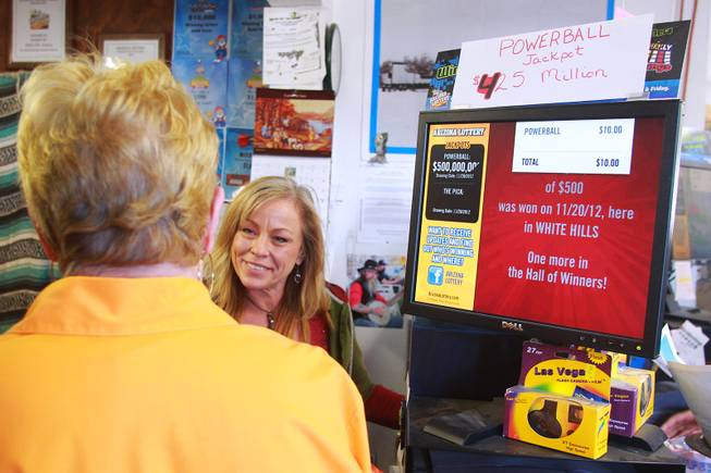 As the jackpot in the multi-state Powerball lottery passes $500 million, Shelia Larson sells tickets to a customer at Rosie's Den in White Hills, Ariz. Tuesday, Nov. 27, 2012.