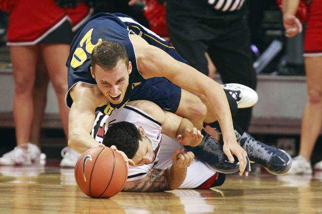 UC Irvine forward Adam Folker falls on top of UNLV forward Carlos Lopez-Sosa while chasing a ball during their game Wednesday, Nov. 28, 2012 at the Thomas & Mack.